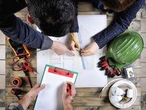 Junge Architekten und Techniker analysieren das Projekt eines Wohnhauses lizenzfreie stockbilder