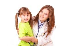 Junge Arztfrau prüft kleines Mädchen stockbild