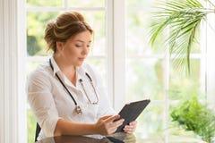 Junge Arztfrauensitzplätze am Tisch mit sthetoscope und Schauen zur Tablette Lizenzfreies Stockfoto