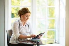 Junge Arztfrauensitzplätze am Tisch mit sthetoscope und Schauen zur Tablette Stockbild