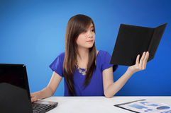 Junge Asiatin beschäftigt, ihre Schreibtischarbeit erledigend stockfoto