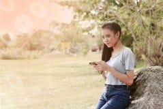 Junge Asiatin, die auf Stein unter Verwendung eines Mobiles sitzt stockfotografie