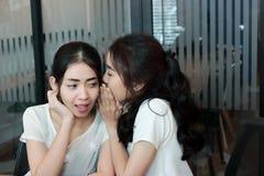 Junge Asiatin, die Klatsch im Wohnzimmer flüstert lizenzfreies stockfoto