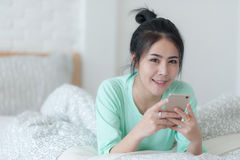 Junge Asiatin, die selfie Foto im Schlafzimmer macht Stockfotografie