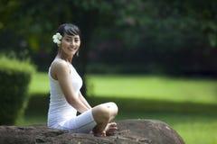 Junge Asiatin, die in Yogasitz lächelt Stockfoto