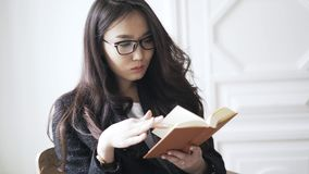 Junge Asiatin, die zu Hause ein kleines orange Buch liest stock video footage