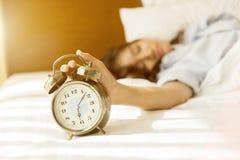 Junge Asiatin im Bett, das versucht, mit Wecker aufzuwachen Lizenzfreie Stockfotos