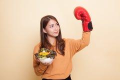 Junge Asiatin mit Boxhandschuh und Salat stockbild