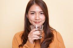 Junge Asiatin mit einem Glas Trinkwasser lizenzfreies stockfoto