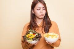 Junge Asiatin mit Kartoffelchips und Salat lizenzfreies stockbild