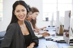 Junge Asiatin mit Kopfhörer lächelnd zur Kamera im Büro lizenzfreie stockfotos