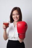 Junge Asiatin mit Tomatensaft und Boxhandschuh Stockfoto