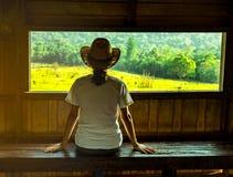 Junge Asiatinabnutzung, die der Hut auf Holzbank und aufpassender schöner Ansicht der grünen Rasenfläche und des Waldes sitzen lizenzfreies stockbild
