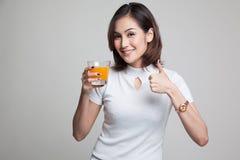 Junge Asiatindaumen trinken oben Orangensaft Lizenzfreie Stockfotos