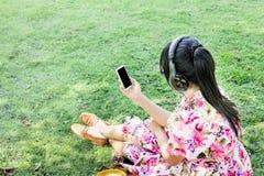 Junge Asiatinnen unterstützen, oder seltene Ansicht hören Musik über headphon Lizenzfreies Stockfoto