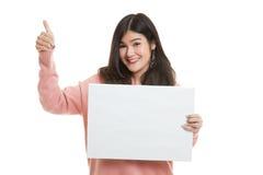 Junge Asiatinshow greift oben mit weißem leerem Zeichen ab Lizenzfreie Stockbilder