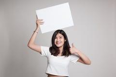 Junge Asiatinshow greift oben mit weißem leerem Zeichen ab Stockfotografie