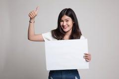 Junge Asiatinshow greift oben mit weißem leerem Zeichen ab Lizenzfreie Stockfotos