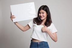 Junge Asiatinshow greift oben mit weißem leerem Zeichen ab Stockfoto