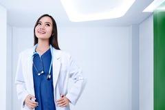 Junge asiatische Ärztin mit weißem Mantel und Stethoskop stockbilder