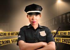 Junge asiatische amerikanische Polizeibeamtestellung ernst im Schutz des Tatorts f?r den Erhalt des Beweises an, nicht Querpolize lizenzfreie stockfotos