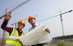 Junge asiatische Architektendiskussionsfront der Baustelle Lizenzfreie Stockfotos