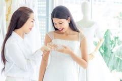 Junge asiatische Braut schaut Perlenhalskette auf ihrer Brautjungfer, die Hände in Heiratsbekleidungsgeschäft für Hochzeitszeremo lizenzfreies stockbild
