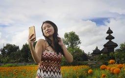 Junge asiatische chinesische touristische Frau, die Selbstporträt selfie Foto mit Handy auf Exkursion durch schönes Blumenfeld ma Stockbild