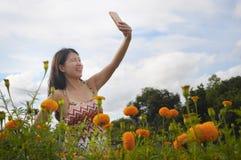 Junge asiatische chinesische touristische Frau, die Selbstporträt selfie Foto mit Handy auf Exkursion durch schönes Blumenfeld ma Lizenzfreie Stockfotografie