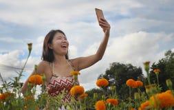 Junge asiatische chinesische touristische Frau, die Selbstporträt selfie Foto mit Handy auf Exkursion durch schönes Blumenfeld ma Lizenzfreie Stockfotos