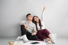 Junge asiatische erwachsene Paare, die auf Flor plant neues Haupt-desig sitzen lizenzfreie stockfotografie