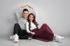 Junge asiatische erwachsene Paare, die auf Flor plant neues Haupt-desig sitzen stockbild