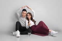 Junge asiatische erwachsene Paare, die auf Flor plant neues Haupt-desig sitzen lizenzfreies stockfoto