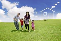 Junge asiatische Familie mit einem gezogenen Haus auf dem Feld Stockfotografie