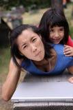 Junge asiatische Familie mit Laptop draußen stockfotografie