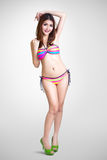 Junge asiatische Frau der hübschen Badeanzugmode, die auf grauem backgro aufwirft Stockbilder