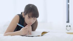 Junge asiatische Frau des schönen Porträts auf denkender Idee des Betts zu Hause liegen und Buch oder Tagebuch in das Schlafzimme stock video footage