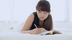 Junge asiatische Frau des schönen Porträts auf denkender Idee des Betts zu Hause liegen und Buch oder Tagebuch in das Schlafzimme stock footage
