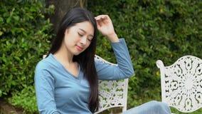 Junge asiatische Frau des schönen Porträts sitzend auf Stuhl mit Lächeln und glücklich am Park, bewegend, Kamera verschiebend stock footage