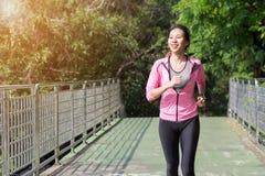 Junge asiatische Frau, die auf Bürgersteig am Morgen läuft stockbilder