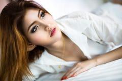 Junge asiatische Frau, die auf dem Bett liegt Lizenzfreie Stockfotos
