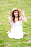 Junge asiatische Frau, die auf dem grünen Gras sich entspannt Stockbilder