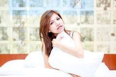 Junge asiatische Frau, die auf ihrem Bett sich entspannt Stockbilder
