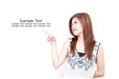 Junge asiatische Frau, die auf weißen Hintergrund zeigt Stockfoto