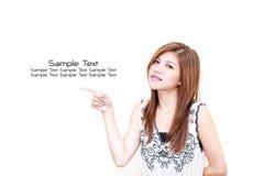 Junge asiatische Frau, die auf weißen Hintergrund zeigt Stockfotografie