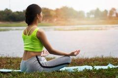 Junge asiatische Frau, die auf Yogamatte, hintere Ansicht meditiert Stockfotografie