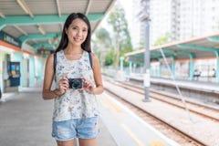Junge asiatische Frau, die Digitalkamera im hellen Bahnhof hält stockbilder