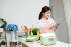 Junge asiatische Frau, die eine digitale Tablette in der Küche verwendet lizenzfreie stockfotos