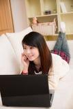 Junge asiatische Frau, die einen Laptop und ein Mobiltelefon verwendet Stockfotografie