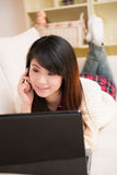 Junge asiatische Frau, die einen Laptop und ein Mobiltelefon verwendet Lizenzfreies Stockfoto